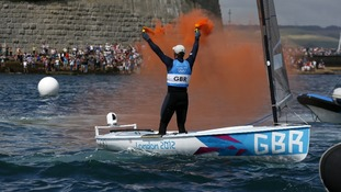 Ben Ainslie holds flares as he celebrates winning the men's finn class one person dinghy (heavyweight) medal race sailing competition.