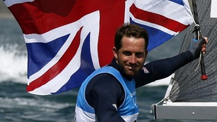Ben Ainslie holds the Union Flag as he celebrates winning the men's finn class one person dinghy medal race sailing contest.