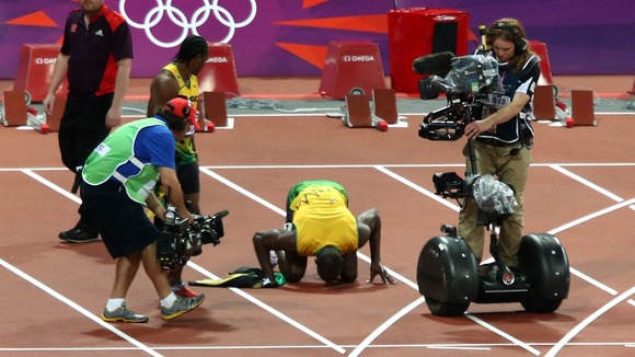 Bolt kisses the 100m track in celebration.