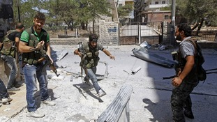 A Free Syrian Army fighter runs for cover during clashes with Syrian Army soldiers in the Salah al- Din neighbourhood of central Aleppo.