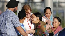 A distraught women is helped to a car outside of the Sikh temple in Oak Creek, Wisconsin.
