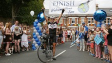 Tom holds his arms aloft in triumph after crossing the finish line in south London.