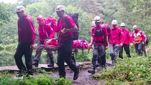 Members of Calder Valley Search and Rescue lift the injured walker down