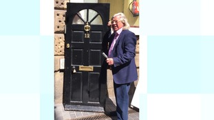 Ian Wallace, owner of The Beatles Shop, with the door to the birthplace of George Harrison taken from 12 Arnold Grove, Liverpool.