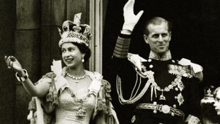 The Queen wearing the Imperial State Crown and the Duke of Edinburgh in uniform on the balcony