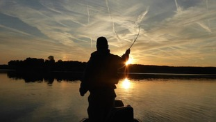 man casting fishing line at sunset