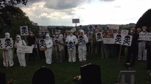 Protesters gathered in white suits and facemasks