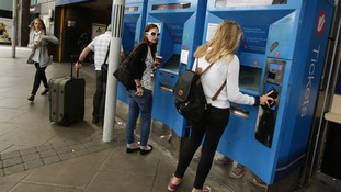 Rail travellers buying tickets.