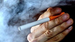 A man's handing holding an e-cigarette.