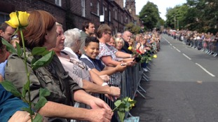 Fans line up through Woolton holding roses