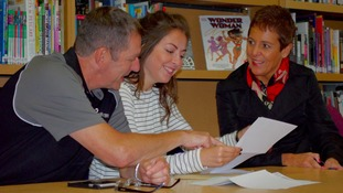 A student opens her results with her parents