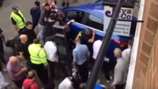 About a dozen men lift the car off the woman who had been trapped after the car reversed into her
