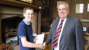 One student shakes hands with the school's headmaster