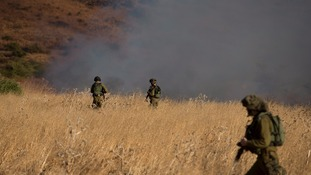 Israeli soldiers patrol next to a smoke from a fire caused by a rocket attack in northern Israel,