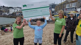 Madison hands over her cheque to Children's Hospice South West.