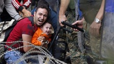 A man holds a child near a police blockade at the Greek-Macedonian border