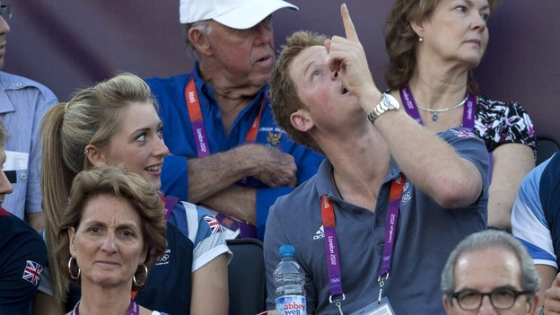 Harry and double-Olympic cycling champion Laura Trott watch the women's beach volleyball bronze medal match.