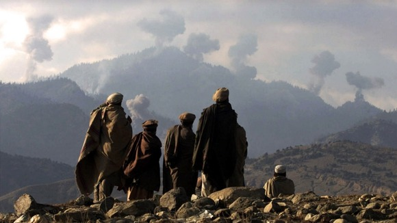 Anti-Taliban Afghan fighters watch explosions from US bombings in the Tora Bora mountains