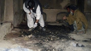 Afghan men investigate at the site of an shooting incident in Kandahar province