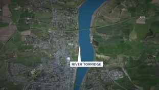 The woman was found unconscious on the banks of the River Torridge