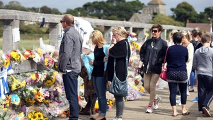 People look at floral tributes left on the Old Tollbridge near the A27 at Shoreham.