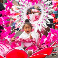 A young girl on a carnival float tricycle during the Notting Hill Carnival.
