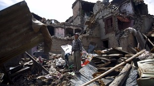 A man stands on the debris of collapsed houses after a 7.3-magnitude earthquake in Nepal this May.