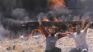 Members of the Free Syrian Army fighters pose near destroyed tank