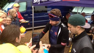 Sir Bradley Wiggins takes time to sign autographs before the race.