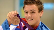 Tom Daley shows off his medal