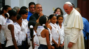 Pope Francis talks with children at the sanctuary.