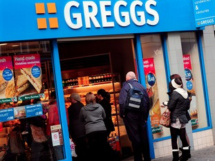 A Greggs shop front with queuing customers