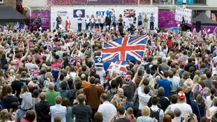 Fans wave at the athletes on stage during a homecoming reception in Millennium Square, Leeds.