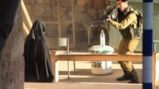 Israeli soldier aims gun at woman