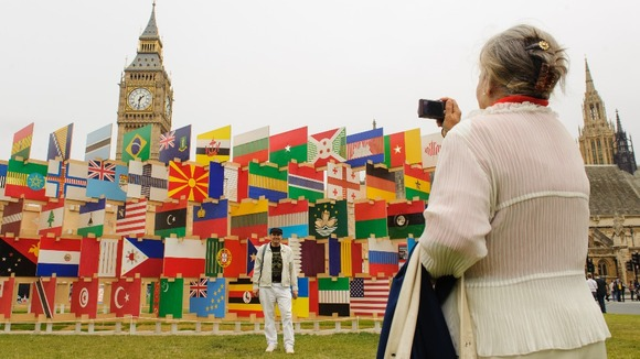 Tourists pose for photographs next to an artwork of national flags in Westminster