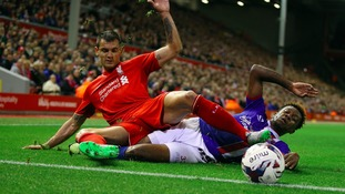 Liverpool's Dejan Lovren (left) and Carlisle United's Alex McQueen battle for the ball.