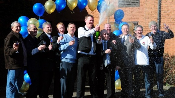 The bus drivers celebrate as they receive the lottery cheque