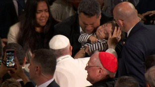 The Pope blesses a child and his family