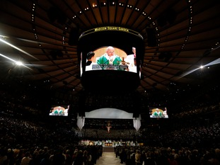 Pope Francis is shown on several large screens as he celebrates mass at Madison Square Garden in New York.