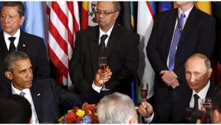 Obama raised a glass with Putin but looked stern as he did so.
