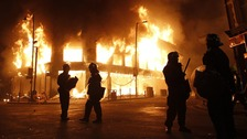 Police officers wearing riot gear stand in front of a burning building in Tottenham, north London August 7, 2011.