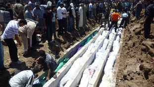People gather at a mass burial for the victims purportedly killed during an artillery barrage from Syrian forces in Houla