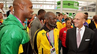 The Duke of Edinburgh talks to Jamaican sprinter Asafa Powell, during a tour of the Athletes Village.
