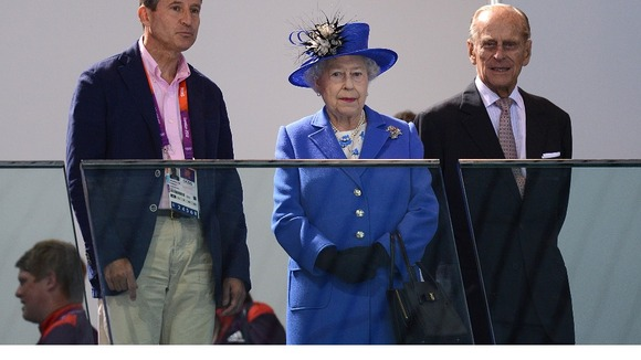 Lord Sebastian Coe, Queen Elizabeth II and the Duke of Edinburgh watch a swimming session at the Olympic Games