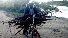 Making the most of what little he has: a young man balances fire wood on his bike
