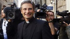 Krzystof Charamsa smiles as he leaves at the end of his news conference in downtown Rome