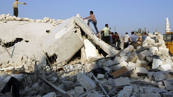 People stand on a house destroyed during a recent Syrian Air force air strike in Azaz