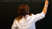 A French teacher writes on a blackboard