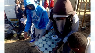 A human chain forms to transport a food donation into the camp