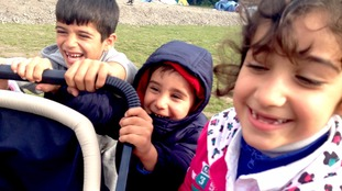 Children laugh and play with a pushchair in the Grand-Synthe camp